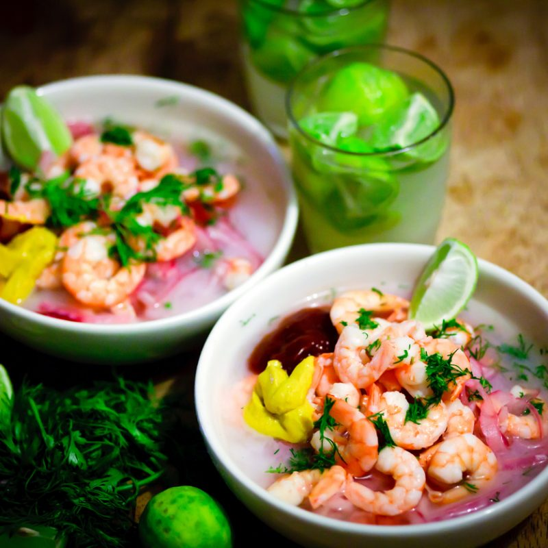 Two bowls of shrimp ceviche with wedges of lime