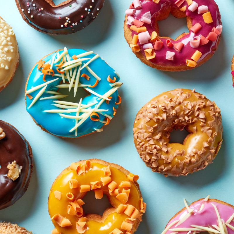 Various donuts on blue background, from above