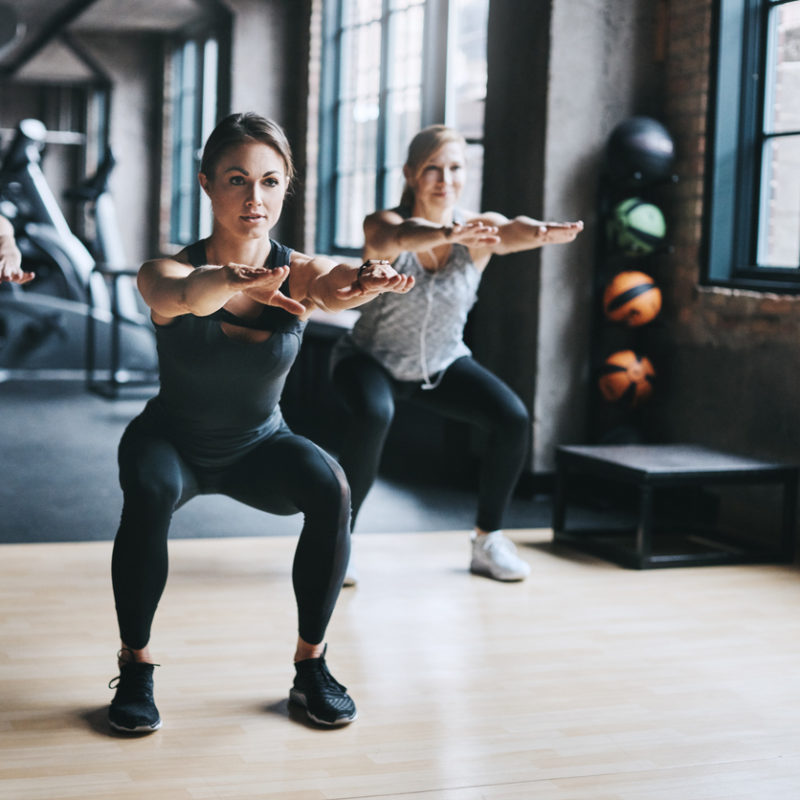 Full length shot of three attractive and athletic women working out in the gym