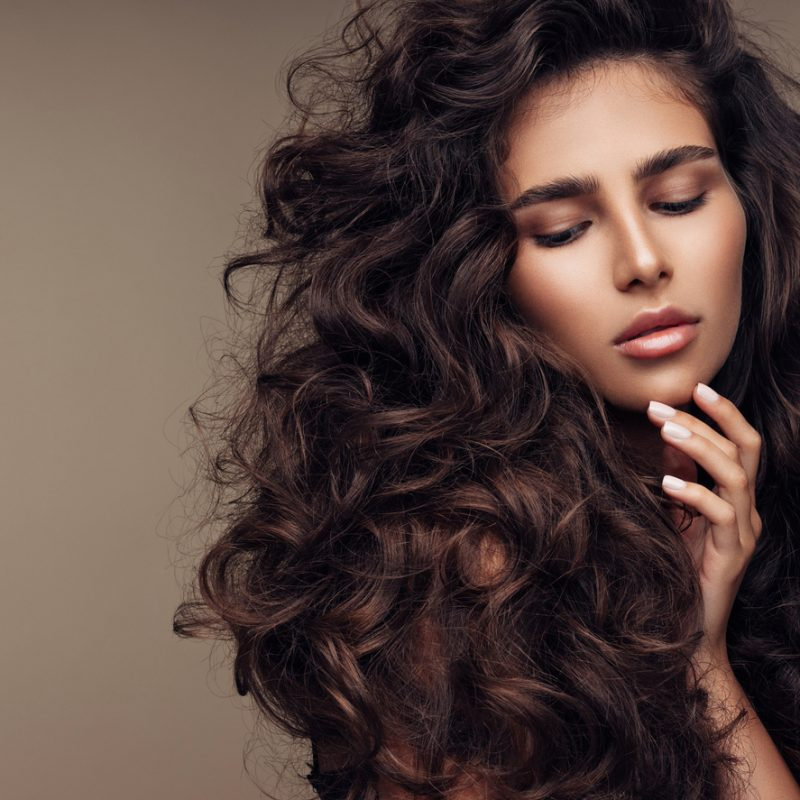 Beautiful girl with lush curly hairstyle