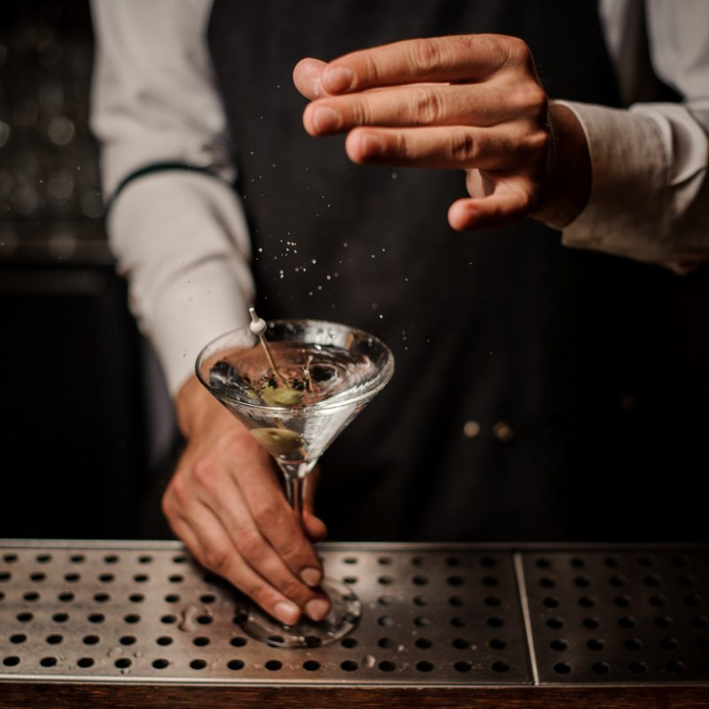 Barman adding salt into a strong martini cocktail