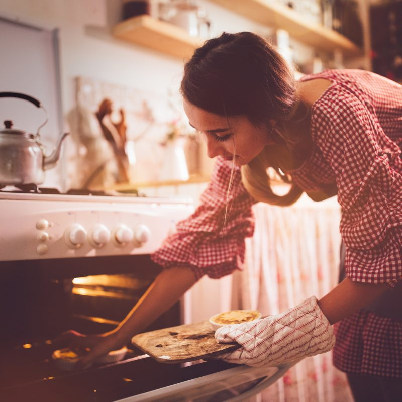 Young woman placing pies in kitchen oven for baking
