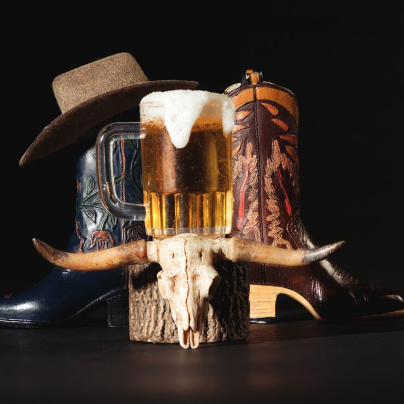 Western Wear Cowboy Tan Hat,  Boots, Cow Skull, Pitcher of Beer on Dark Background