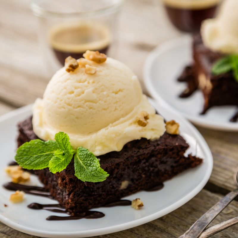 Chocolate brownie with vanilla ice cream, nuts and mint, served om white plate, rustic wood background